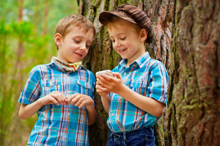 The boy is showing his brother different games on mobile phone