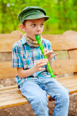 Young stylish kid plays on green recorder