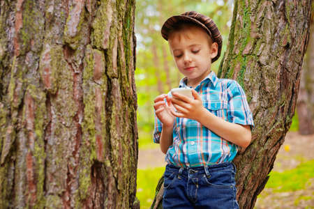 Young boy browses internet on his phone photo