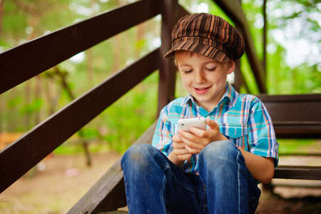 browses: Young stylish boy browses internet on his mobile phone