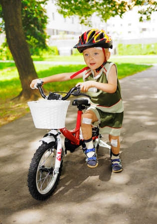 Young cute kid learning to ride a bike photo