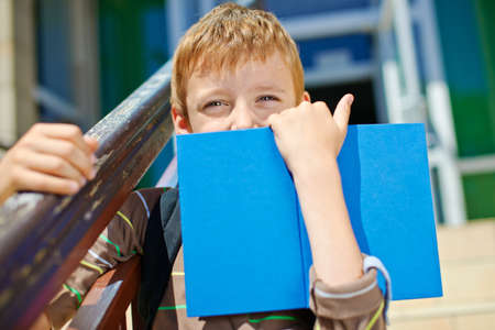 going places: Young secretive boy with book in front of school