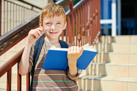 going places: Young thoughtful boy with book on school stairs