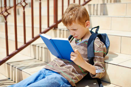 going places: Young boy reading book on school stairs