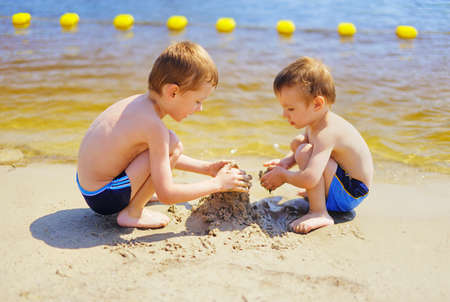 Two cute kids building sand castle on the beach photo