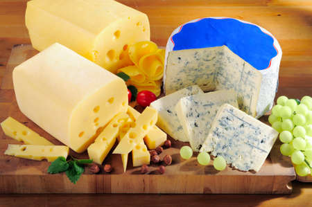 Various types of tasty cheese on cutting board  photo