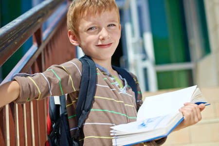 Young kid with book in front of school building photo