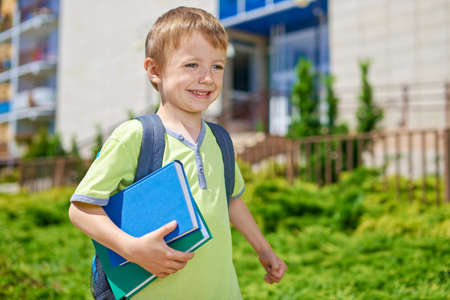 Young happy boy with books in front of school building