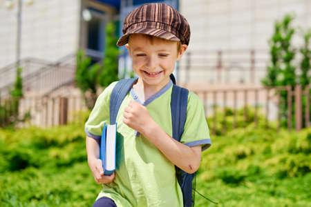 ni�os saliendo de la escuela: Lindo chico joven con el libro en frente del edificio de la escuela Foto de archivo