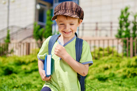 Young cute kid with book in front of school building