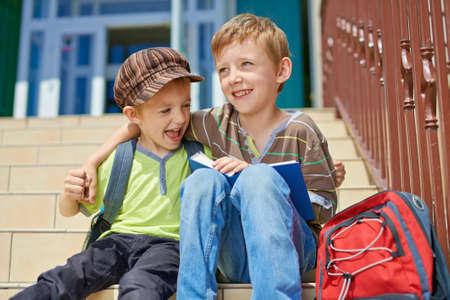 Two happy brothers with book and backpack on stairs in front of scholl