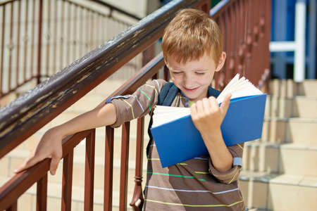 going places: Young happy kid reading book on school stairs Stock Photo