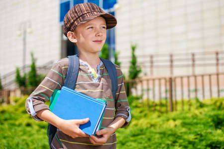 Young pensive kid in front of school building