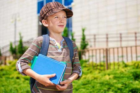 Young pensive kid in front of school building