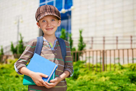 going places: Young cheerful schoolboy with books in front of school building