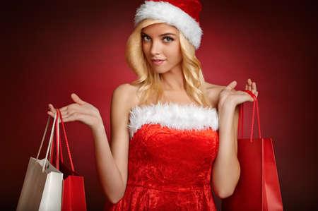 Beautiful santa claus girl with gift bags  Banco de Imagens