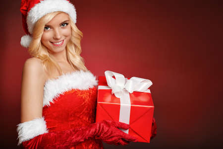 Attractive blonde girl wearing Santa Claus costume and holds gift box  Woman s portrait on dark red with copy space for text  photo