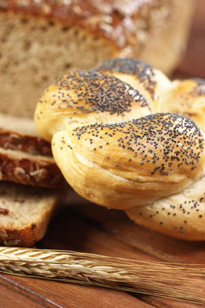 Kaiser bread roll with poppy seeds on wooden table  Bakery products with ear of rye  photo