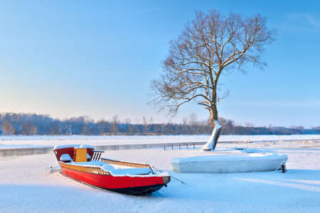 landscape riverside: Winter landscape with boats on the frozen river and one bare tree at riverside  Stock Photo