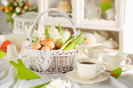 Easter basket full of eggs on a white festive table.