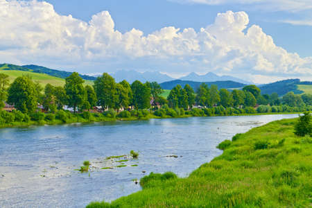 Spring landscape with Tatra Mountains over The Dunajec River. Poland and Slovakia national border view from Sromowce Nizne.