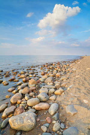Beautiful seascape with coastal stones at the ocean beachand clouds on the blue sky  The Baltic coast, mediterranean sea, Poland  Banco de Imagens