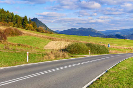 Asphalt Road by The Pieniny Mountains landscape, Carpathians  Daylight scenery with way in the environment of trees, meadows, moutains and clouds on blue sky  Banco de Imagens