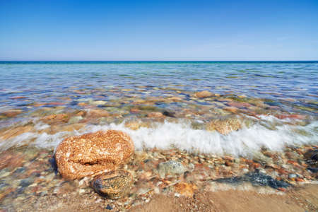 Wave splash  Stones at the ocean shore  The Baltic Sea, mediterranean sea, Poland  Blue sky
