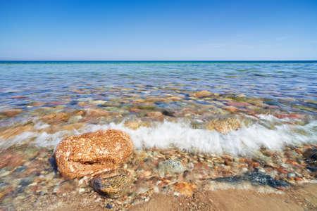 Wave splash  Stones at the ocean shore  The Baltic Sea, mediterranean sea, Poland  Blue sky Banco de Imagens - 29394647