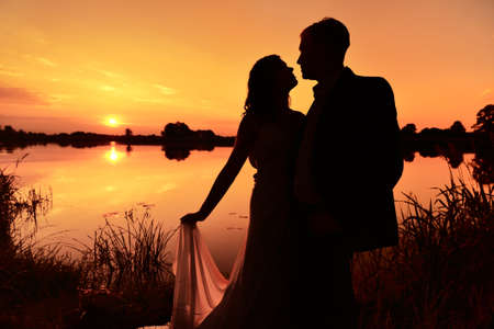 Newlywed couple hugging each other lovingly at sunset.
