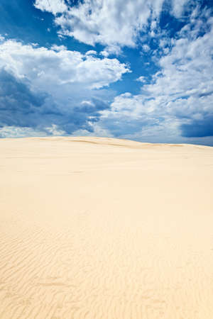 Sand dunes in the Slowinski National Park, Poland. Clouds blue sky desert background.