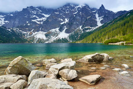 Stones at a shore of the Morskie Oko lake in the High Tatra Mountains. National park, Carpathians, Poland.