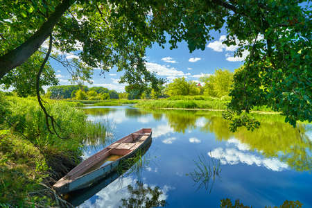 Spring summer landscape blue sky clouds Narew river boat green trees countryside grass Poland water leaves