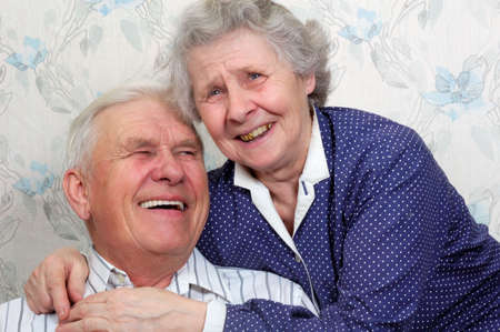 old man smiling: portrait of happy old couple laugh until one cries