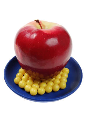plateful: blue plateful of yellow drops vitamin and red apple above them. isolated over white Stock Photo