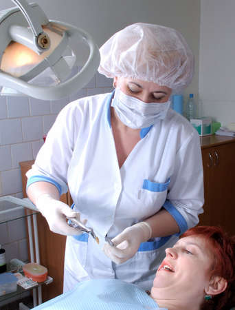 doctor to extract a wisdom tooth and woman with open mouth look at tooth         photo