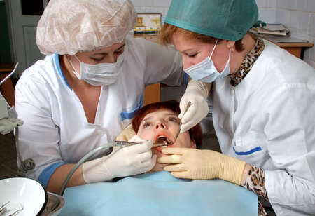 Woman with open mouth look at doctor. Doctor to drill a tooth. Nurse to help a doctor. photo