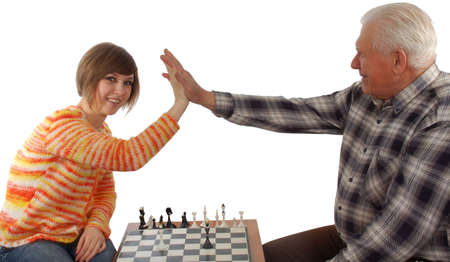 compromise: grandad and granddaughter make a compromise in chess game. isolated on white Stock Photo