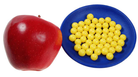 plateful: blue plateful of yellow drops vitamin and red apple. isolated on white