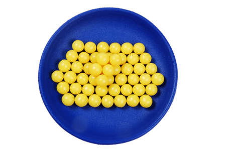 plateful: blue plateful of yellow drops vitamin. isolated on white