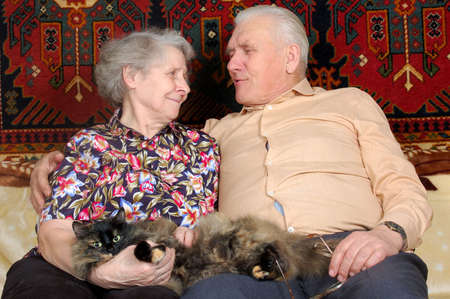 happy seventy year old couple with cat photo