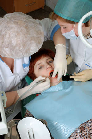 Woman with open mouth look at camera. Doctor to drill a tooth. Nurse to help a doctor. photo
