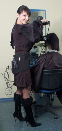barber makes a hair-dress to the young brunette photo