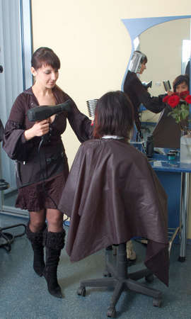 barber makes a hair-dress to the young brunette Stock Photo - 4259560