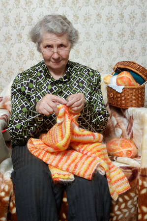 spectacled grandmother binds cardigan