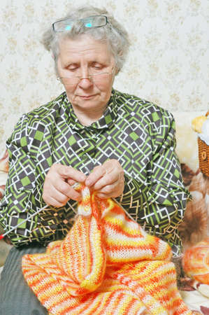 spectacled: spectacled old woman binds cardigan Stock Photo