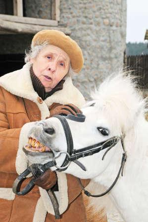 grandmother near funny pony; outdoor photo