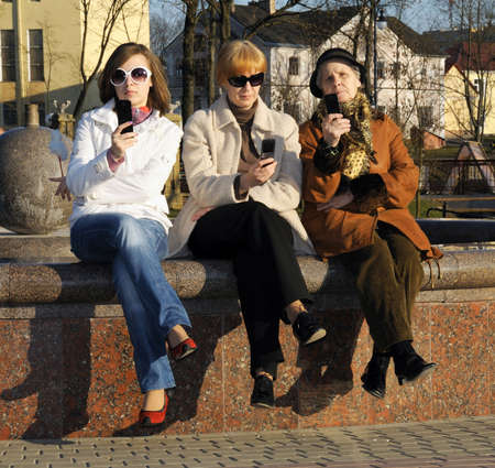 Family of mother, granddaughter and granny with mobile sellphones photo