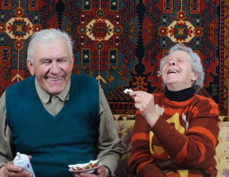 two smiling senior eating dessert photo