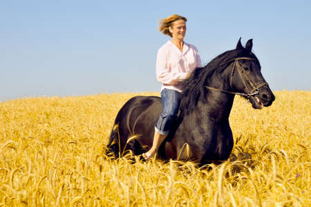 scamper: Beautiful smiling woman rides a pretty horse in field